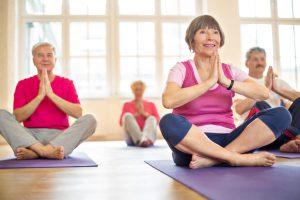 Group of happy seniors practising yoga at health club
